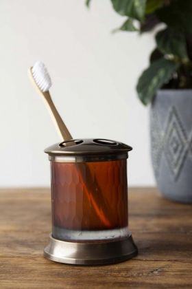 lifestyle image of Apothecary Style Toothbrush Mug with plant in vase in background on wooden table and pale wall background