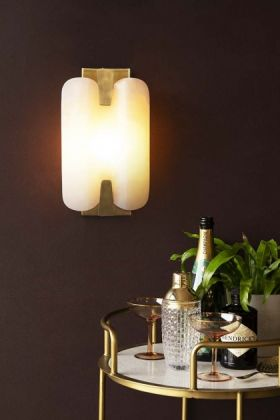 Lifestyle image of the Art Deco Marble Plate Wall Light switched on with full gold and marble drinks trolley and dark wall background
