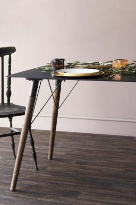 Lifestyle image of Artist's Bench Dining Table with black dining chair and tableware on dark wooden flooring and pale wall background