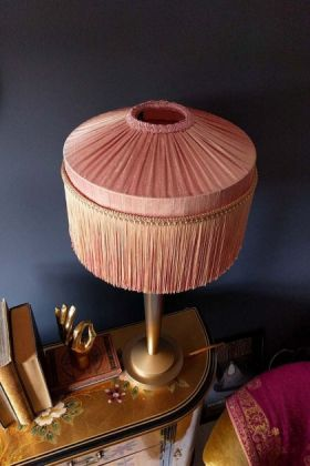 Lifestyle image of the Bespoke Blush Pink Silk Tiffany Lamp Shade with straight fringe on wooden side table with books on top with dark blue wall background