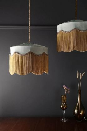 Lifestyle image two of the Bespoke Spearmint Silk Tiffany Lamp Shade with wavy fringed on pendant lights over wooden surface with two vases and dark wall background