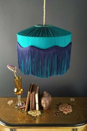 Lifestyle image of the Bespoke Teal Silk Tiffany Lamp Shade with wavy fringe over chest of drawers with ornaments on with dark wall background