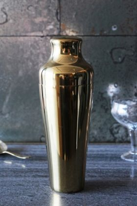 lifestyle image of Belmont Gold Plated Cocktail Shaker on grey table with cocktail glass and antique mirror wallpaper