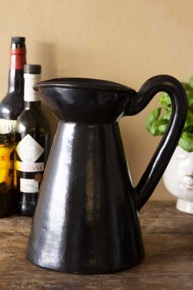 Lifestyle image of the Black Brown Terracotta Jug - Large on crowded wooden shelf and pale wall background
