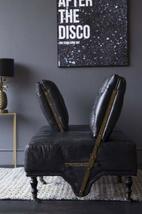 Side angle lifestyle image of the Black Leather Loveseat Sofa with alternate backs on top of natural coloured rug and side table with black table lamp in background and  Unframed After The Disco Art Print on grey wall background