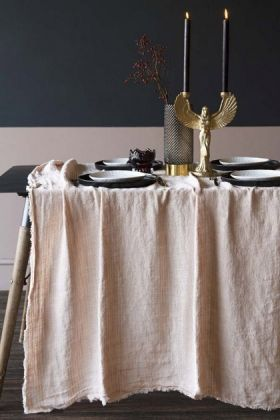 lifestyle image of Blush Pink Woven Linen Tablecloth on set table with tableware, Beautiful Dinner Candle - Black inside Phoenix Candle Holder with contrasting wall background
