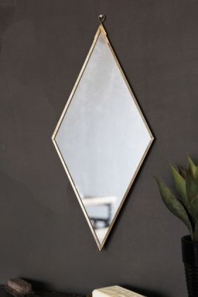 lifestyle image of Brass Effect Diamond Shape Mirror on brown wall background and plant