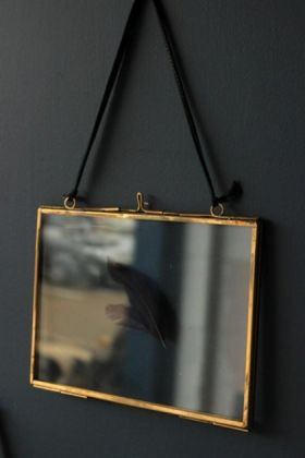 5x7 brass and glass landscape picture frame with a black feather inside on dark background lifestyle image