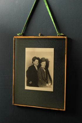 8x10 brass and glass picture frame with a black and white photo of laurel and hardy in it on with green ribbon on dark wall on own lifestyle image