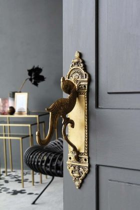lifestyle image of Brass Parrot Design Door Handle Wall Hook on grey door with console table and grey wall background