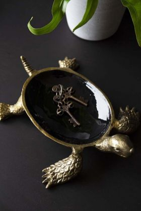lifestyle image of Brass & Black Enamel Turtle Trinket Dish with keys inside and plant in background on black table