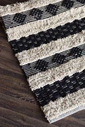 lifestyle image of Casablanca Natural & Black Moroccan-Style Cotton Rug on dark wooden flooring