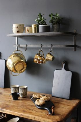 lifestyle image of charcoal grey luggage rack with hooks in crowded kitchen over wooden worktop and gold pans hanging from hooks with dark grey wall background