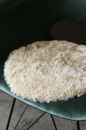lifestyle image of Circular Sheepskin Wool Pad - Bamboo Taupe on green chair with concrete flooring