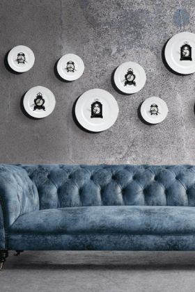 lifestyle image of Clock Plate Clock on distressed grey wall above blue suede look sofa