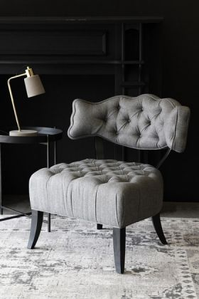 lifestyle image of Cloud Herringbone Tweed Chair - Garson Grey with black side table and table lamp on grey rug and dark wall background