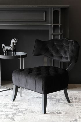 lifestyle image of Cloud Velvet Chair - Back to Black with black side table and unicorn ornament with grey patterned rug and black wall background
