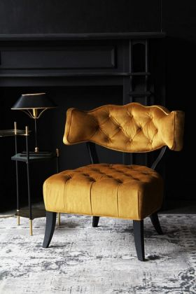 lifestyle image of cloud velvet chair - golden glow with black side table and black and gold table lamp with black fireplace in background