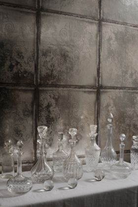 Close-up lifestyle image of the Cole & Son The Albemarle Collection - Albery Wallpaper - Silver with range of clear vases and bottles on white table