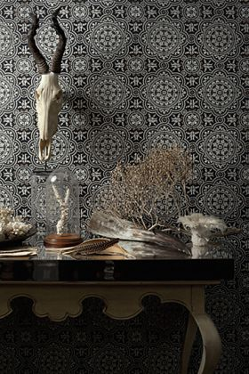 lifestyle image of Cole & Son The Albemarle Collection - Piccadilly Wallpaper - Black & White 94/8045 - ROLL with wooden table and skull with horns on wall