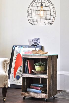 lifestyle image of Crate Side Table By Ines Cole with books and plant inside with wire cage ceiling light above and picture frame leaning against white wall in background