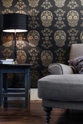 lifestyle mage of day of the dead skull wallpaper - gold & black with grey armchair and black side table with black table lamp on top