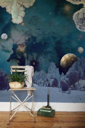 lifestyle image of elli popp de la terre a la lune - from the earth to the moon wallpaper with white chair and plant in pot and green books in pile with black candlestick on wooden flooring