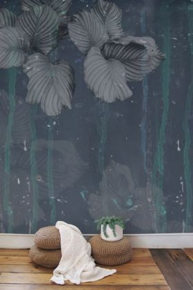 lifestyle image of elli popp issey - nymph on the waters wallpaper - grey with rattan pouffe's and white blanket with plant in white pot