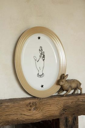 Lifestyle image of the Enchanted Hand Oval Serving Plate displayed on a rustic wooden mantelpiece with rabbit ornament and pale wall background
