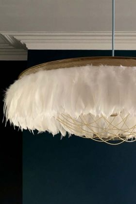 lifestyle image of Fabulous Feather Chandelier Featuring Chains - Gloria - White with dark blue wall background