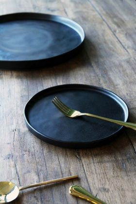 lifestyle image of Faria Black Side Plate with gold fork and other cutlery on wooden table