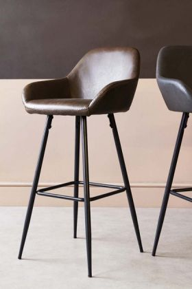 lifestyle image of Faux Leather Bar Stool With Zig Zag Stitching - Brown with second stool in background on pale wooden flooring and contrasting wall background