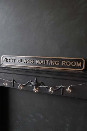lifestyle image of First Class Waiting Room Sign on black shelf with tassel decoration