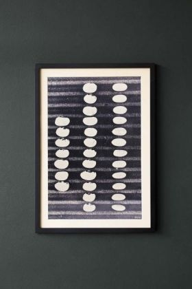 lifestyle image of Framed Abstract Pebble Art Print hung on dark grey wall background