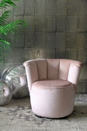 lifestyle image of gallery velvet cocktail chair - blush pink with disco balls and plant on grey patterned rug and grey tiled wallpaper background