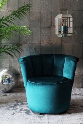 lifestyle image of gallery velvet cocktail chair - ocean deep green with cage ceiling light and plant with disco ball in background