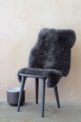 genuine sheepskin rug - silky dark grey on grey chair with large pot and pale background lifestyle image