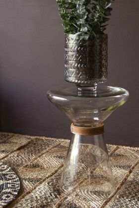 Lifestyle image of the Glass Side Table With Leather Detail with plant inside and on woven surface and dark wall background