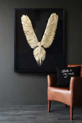 lifestyle image of Gold Feather Wings In Frame with brown leather chair with black cushion and grey wall background