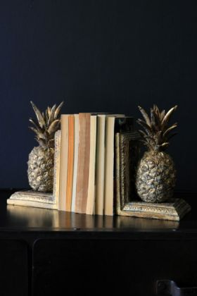 lifestyle image of gold pineapple bookends with books in between on black table and dark wall background