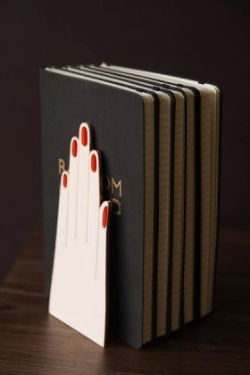Lifestyle image of the Handy Hands Bookends with books inside and dark wall background