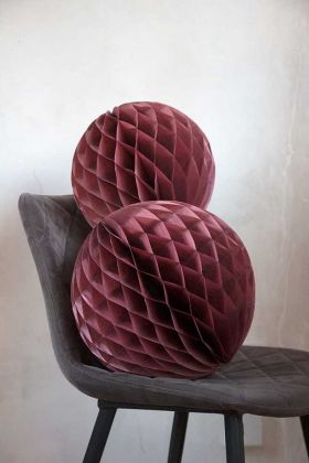 Image of the Set Of 2 Honeycomb Ball Decorations In Berry Pink on a chair