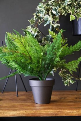 lifestyle image of Indoor/Outdoor Faux Potted Fern on wooden table with ivy in black pot and grey wall background