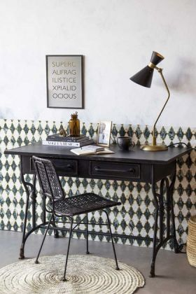 Lifestyle image of the Black Metal Sideboard Desk with table lamp and black chair on patterned wallpaper wall background and jute rug on floor