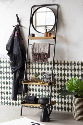 Lifestyle Image of the Industrial-Style Ladder Shelf Unit With Round Mirror filled with accessories with a coat hook and house plant on monochrome patterned wall background