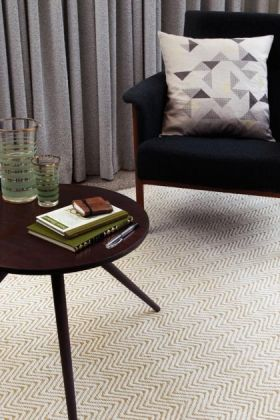 lifestyle image of ives cotton and jute rug with black armchair with cushion and round wooden coffee table