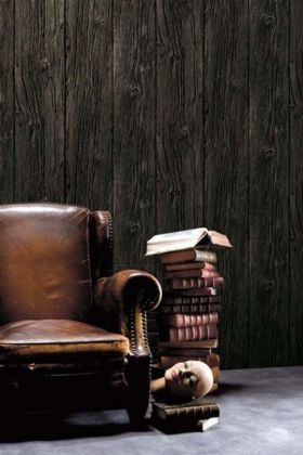 lifestyle image of Koziel Charred Wood Boarding Wallpaper with brown leather armchair and pile of books on grey flooring