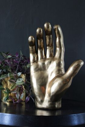 lifestyle image of large gold decorative hand ornament on black table with plant and dark wall background