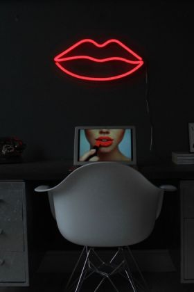 lifestyle image of LED Neon Light - Lips - Red over black desk and chair and black wall background