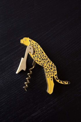 lifestyle image of the Leopard Bottle Opener & Corkscrew on a dark surface background